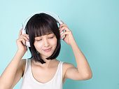 Asian woman enjoy music with headphone   , isolated on blue background