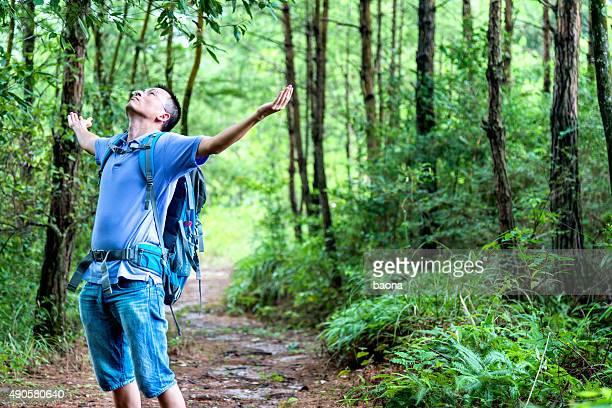 Asian woman enjoying fresh air in forest