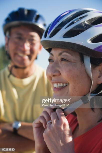 Asian woman fastening bicycle helmet