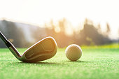 Asian woman Golf player hit swing shot golf ball on the green sunset eventing time.  Healthy and Lifestyle Concept.