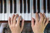 Asian Woman hands playing the piano in top view