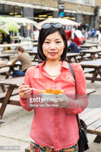 Asian woman hodling noodle dish at outdoor market. : Stock Photo