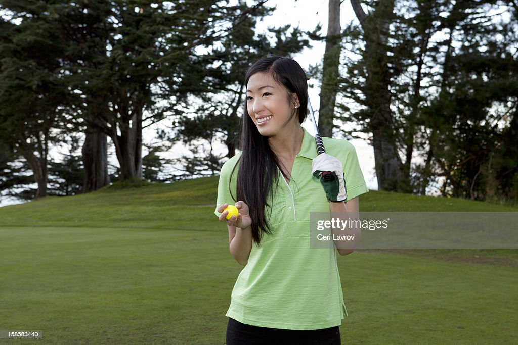 Asian woman holding a golf ball and club : Stock Photo