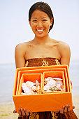 Asian woman holding box of seashells
