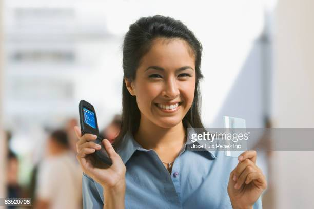 Asian woman holding cell phone and credit card
