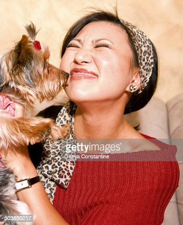 Asian woman holding dog on sofa