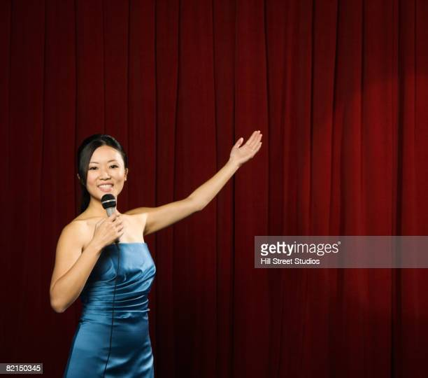 Asian woman holding out arm on stage