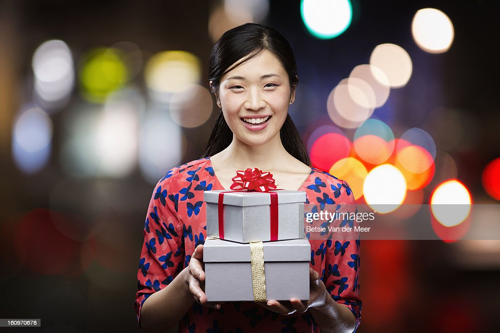 Asian woman holding presents,smiling. : Stock Photo