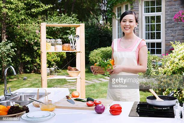 Oriental woman holding the vegetables in the outdoor kitchen