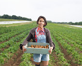 Asian woman holding tray of potatoes on farm.