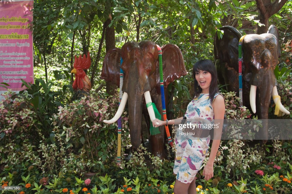 Asian woman holding tusk of elephant tusk : Stock Photo
