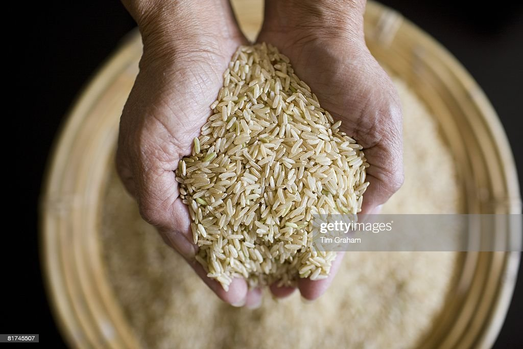 Asian woman holds handful of wholegrain rice, Rice has become an expensive commodity as its in short supply