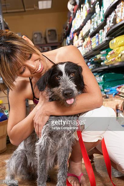 Asian woman hugging dog in pet store