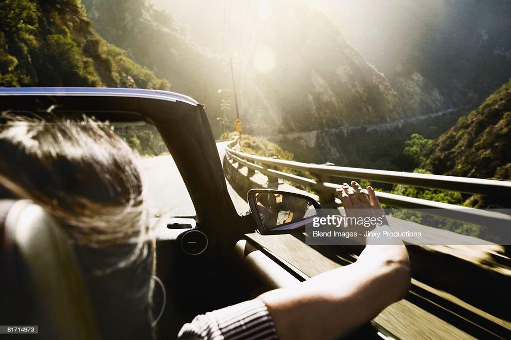 Asian woman in convertible car