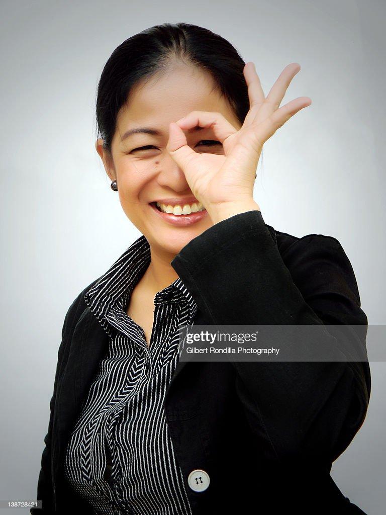 Asian woman in corporate attire looking through fi : Stock Photo