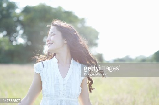 Asian woman in countryside with eyes closed.
