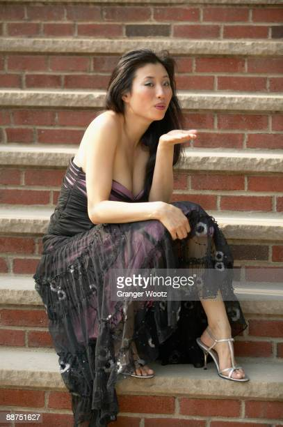 Asian woman in evening gown blowing kisses