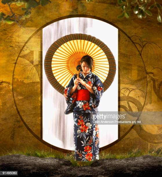Asian woman in geisha dress holding parasol