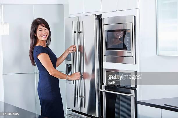 アジア女性のオープンキッチンの冷蔵庫