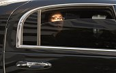 Asian woman in limousine with window part of the way down