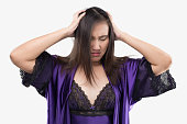 Asian woman in satin nightwear and purple robe suffering from a headache at night. Sleeping problems, Girl in silk nightgown with a headache holding her hand to the head on a gray background, Sleeples