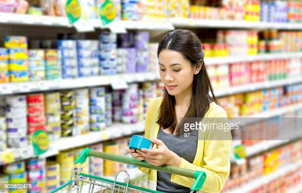 Asian woman in the supermarket to buy canned