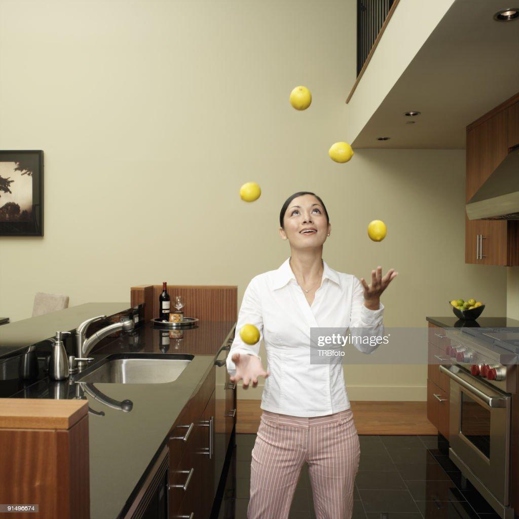 Asian woman juggling lemons in kitchen : Stockfoto