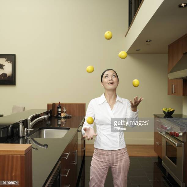 Asian woman juggling lemons in kitchen
