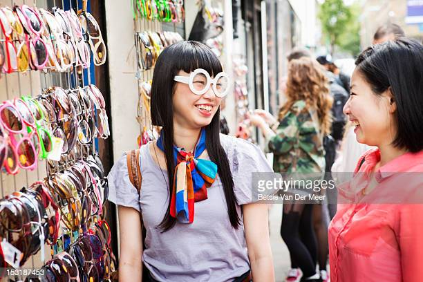 asian woman laughing at friends choice of glasses.