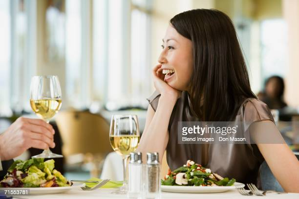 Asian woman laughing at restaurant