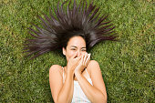 Asian woman laying in grass