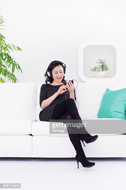 Asian Woman Listening to Music with Mobile Phone