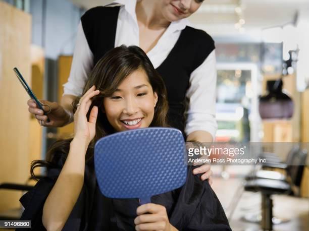 Asian woman looking at hair in salon