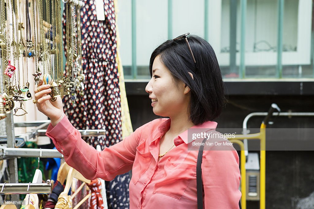 Asian woman looking at jewellery at market stall. : Stock Photo