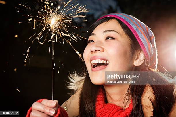 Asian woman looking at sparkler,nighttime.