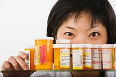 Asian woman looking over bottles of medication