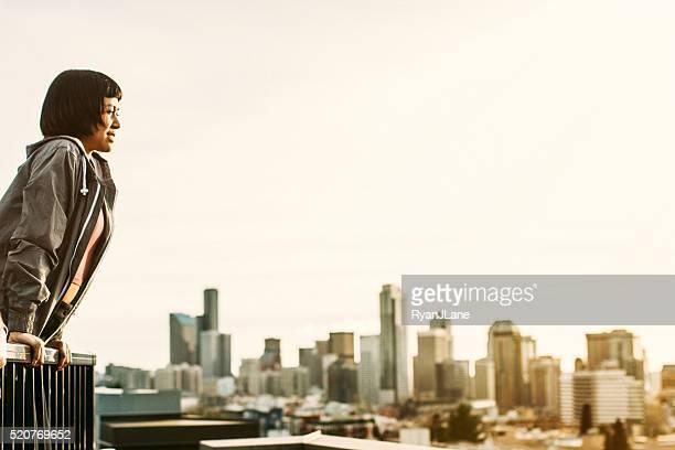 Mujer asiática en el último piso con vista de los edificios de la ciudad de Seattle