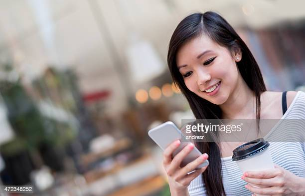 Asian woman on the street texting and drinking coffee