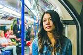 Asian woman on the tube in London. Beautiful young woman portrait, looking away from camera and leaning into the train while commuting. Lifestyle and transport concepts