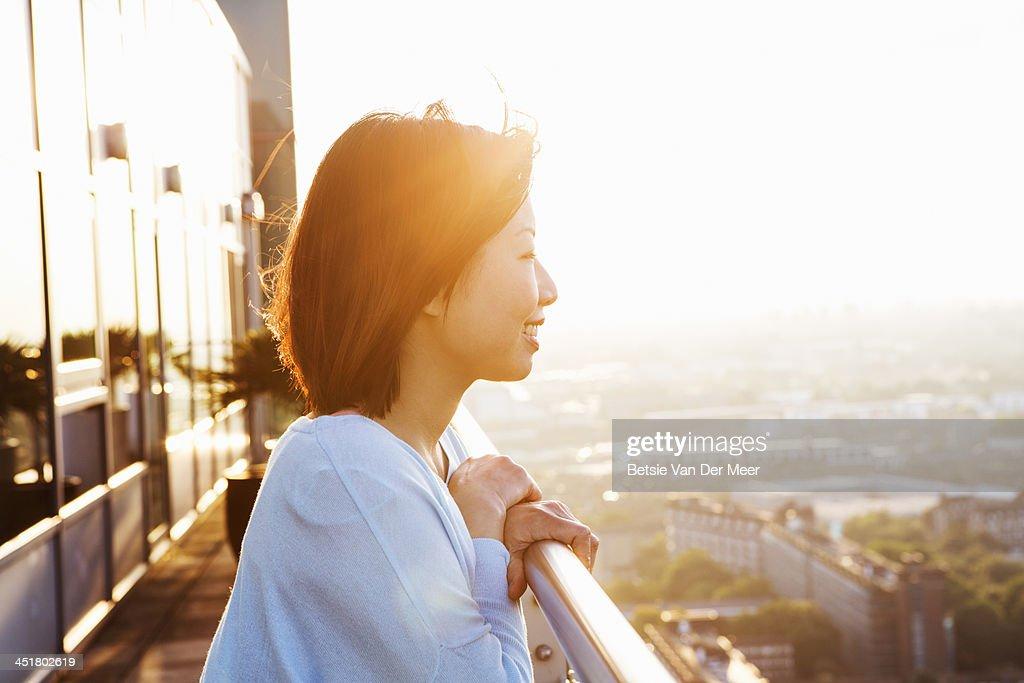 Asian woman overlooks city at sunset.