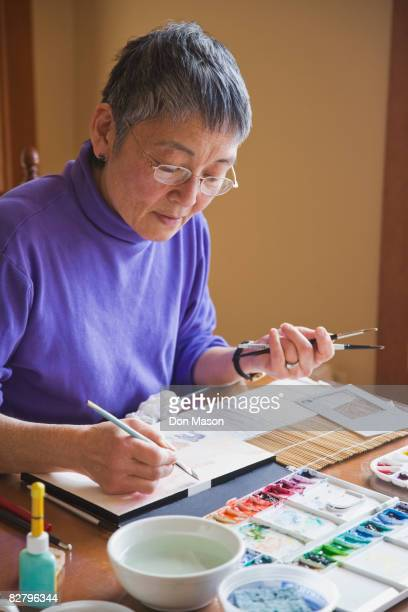 Asian woman painting at table