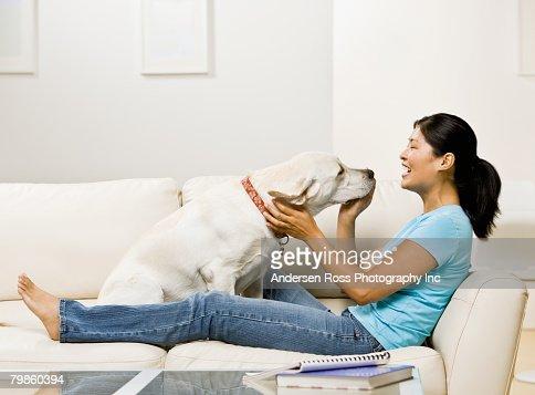 Asian woman petting dog : Stock Photo