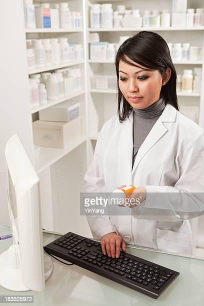 Asian Woman Pharmacist Filling Prescription in Retail Pharmacy Drug Store