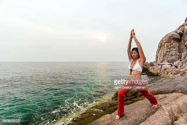 Asian woman practicing yoga outdoors on island in southern Thailand