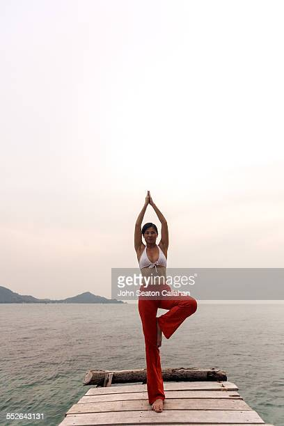 Asian woman practicing yoga outdoors on pier in southern Thailand