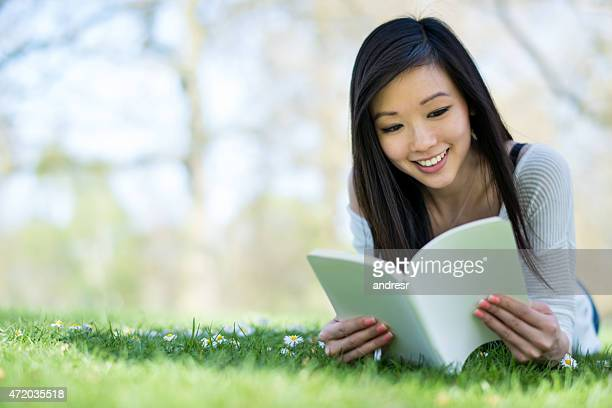 Asian woman reading at the park