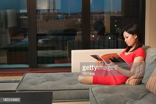 Apartment Inside Night asian woman reading magazine on sofa inside apartment at night