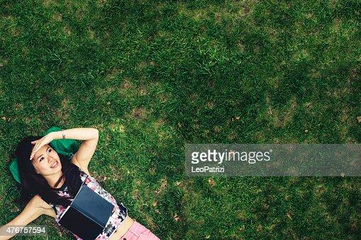 アジア女性のためのリラックスした公園で、横たわっている