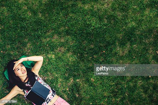 Asian woman relaxed laying down in the park