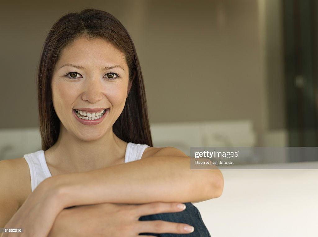 Asian woman resting arm on knees : Stock Photo
